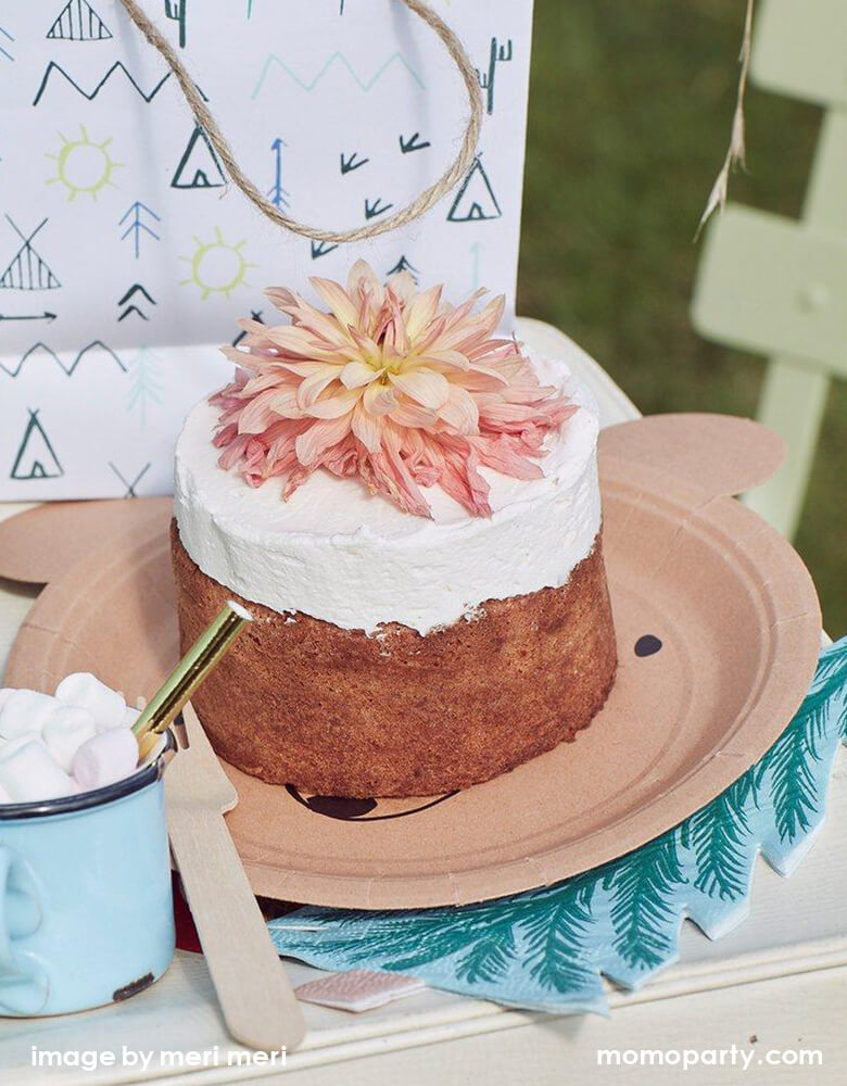 close up of Woodland Camping outdoor party with a flower cake on top of Meri Meri Bear Small Plates and tree Napkins, lets go explore party bags, a blue vintage with mini marshmallows