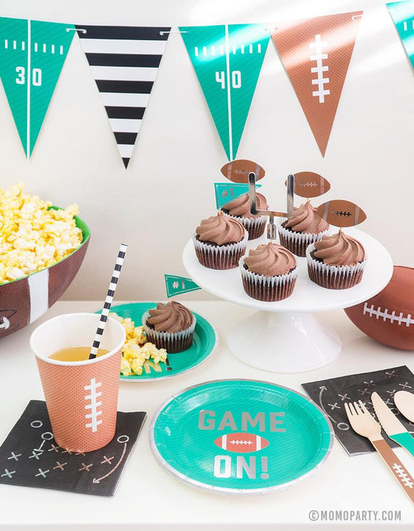 Super Bowl Football Party table set up idea with Green Game on Football Party Appetizer Paper Plates, Black Game Play Appetizer Napkins, 12 oz Football design Party Paper Cups, chocolate Cupcake with Tailgate Treat Picks, Football Tailgate Party Banner, Popcorn in a bowl