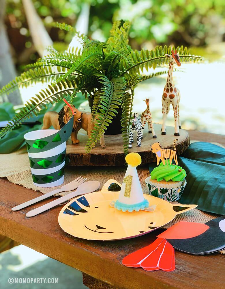 Safari Jungle Outdoor Party Table Set Up with Tiger Paper Plates,  Toucan Napkins, Snake paper cups, animal figure toys, get wild cupcake kit, 1 year birthday hat on a wooden picnic table.