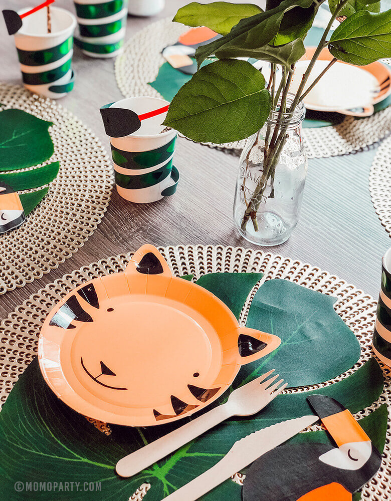 Safari Jungle Party ideas of Table decoration with tiger paper plates, toucan napkin, palm leaves as table mat, snake paper cups