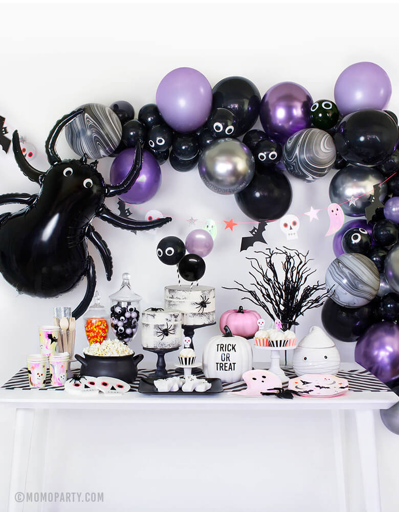 "Momo Party Modern Halloween party in a box, party look with balloon garland, Meri Meri Spider Foil Mylar Balloon, halloween icon garland, table set up with MeriMeri Iridescent Ghost Plates, Halloween Icons Side Plates and cups, skull napkin, naked cake with spiders, googly eyes with gum balls in a jar, pink pumpkin decor, white pumpkin with ""Trick or Treat"", black witch pot with popcorns, party inspiration for for halloween party, trick-or-treat Halloween party, Haunted House Birthday Party, Witch Party"