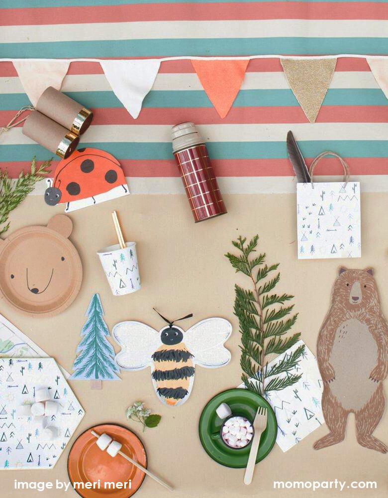 Woodland Camping party tabletop filled with Meri Meri Bear Small Plates, Ladybug Napkins, Meri Meri Bee Plates, Brown Bear plate, Let's Explore Large Plates napkin and cups, Let's Explore party bag with a feature inside, s'mores, a small cup of hot chocolate with marshmallow, color stripe tablecloth and a kid telescope, enjoy the fun with this modern look and fun designed woodland camping party for your summer holiday