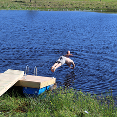 man diving into creek from pontoon