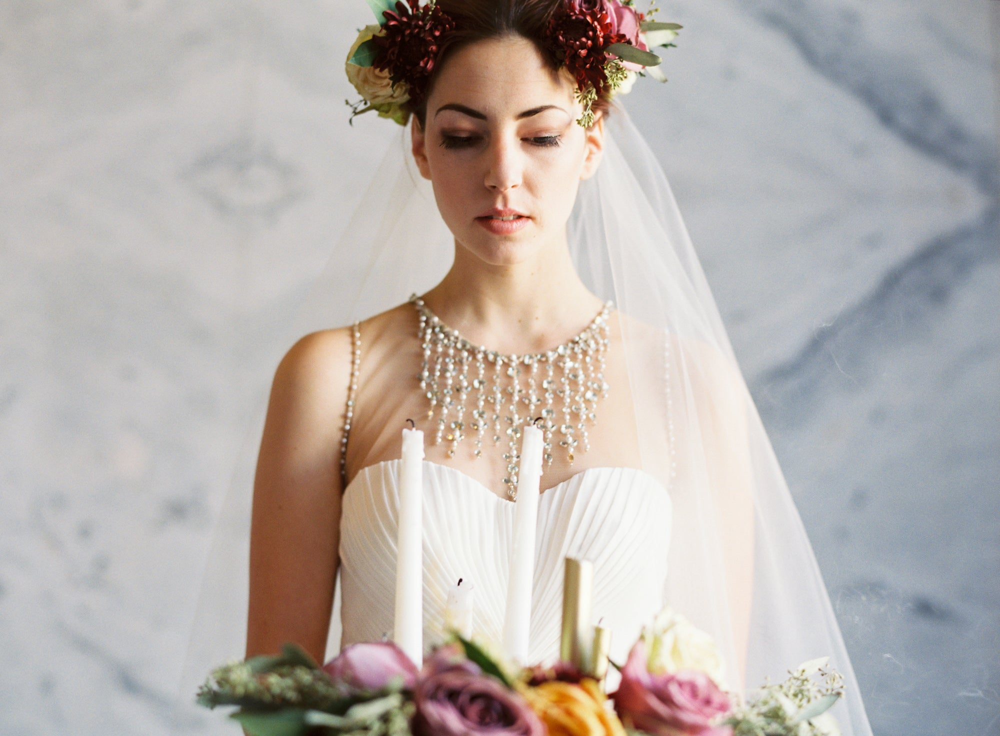 Bride with flower wreath crown and veil holding candles