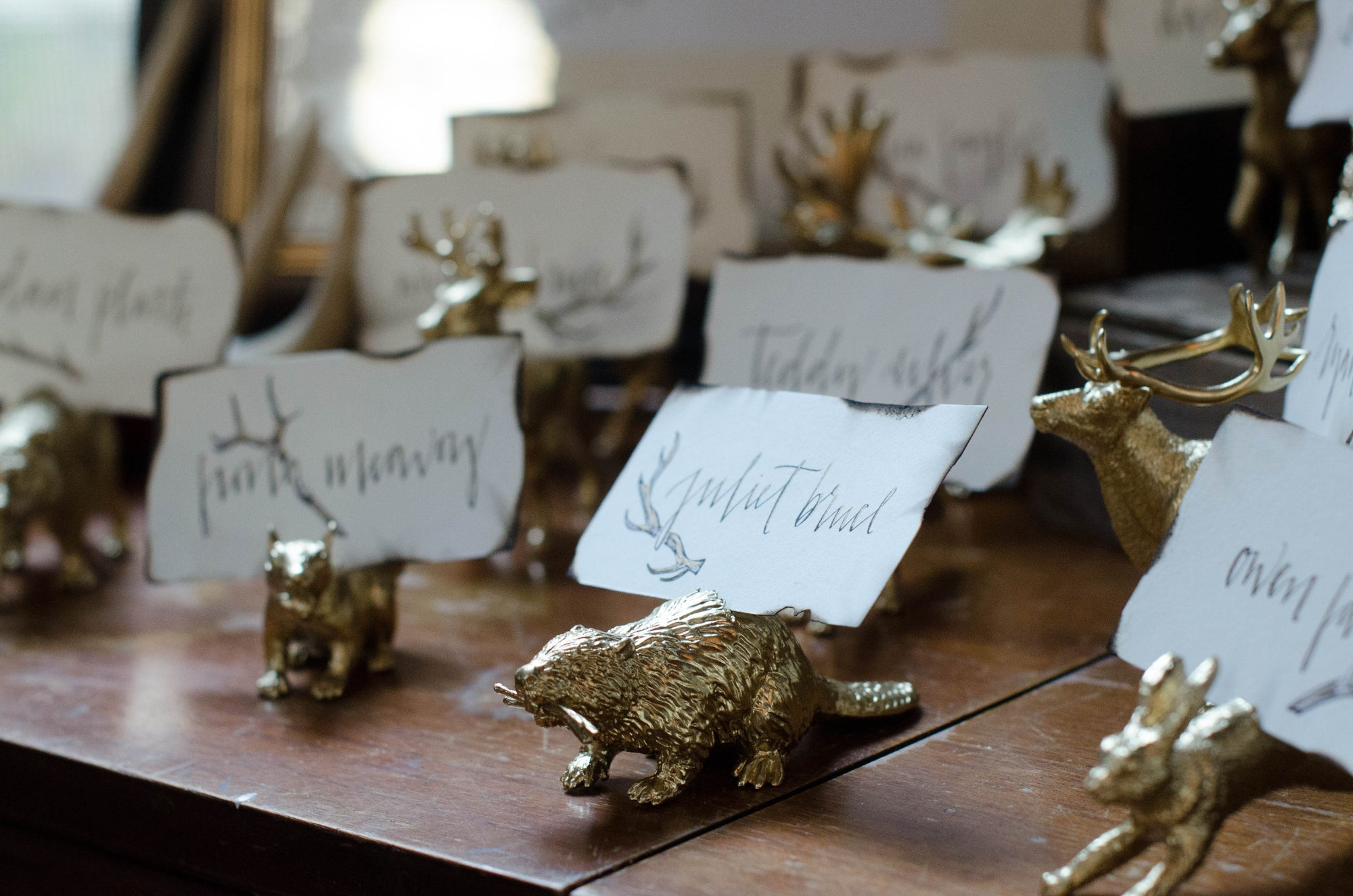 These gold animal place card seating card holders with hand lettered calligraphy are perfect for a rustic woodland wedding and so cute for guests to take home as a gift!