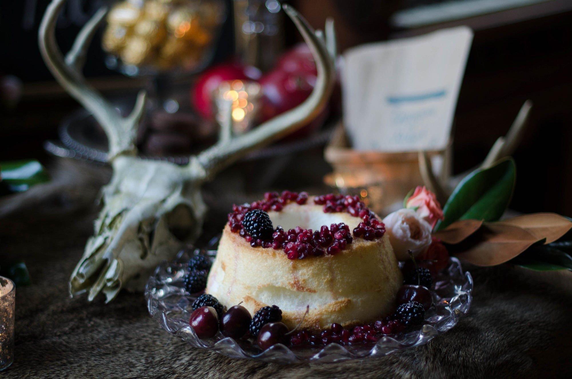 This rustic berry angel food cake from a woodland inspired wedding looks glamorous on the dessert table with a taxidermy stag skull