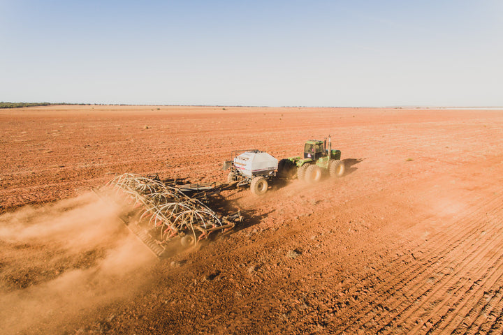 John Deere tractor seeding barley in a red dirt paddock