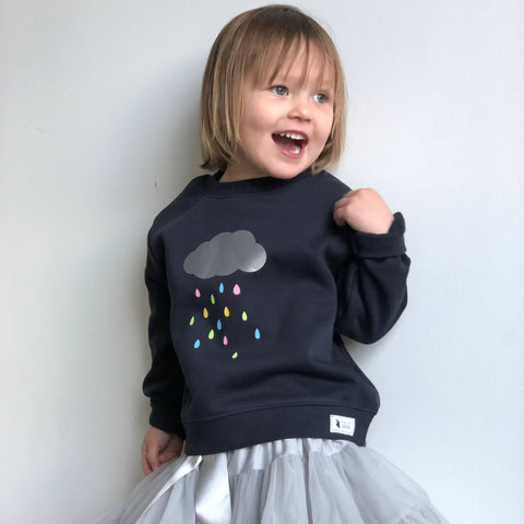 girl wearing navy cloud rain jumper and silver tutu