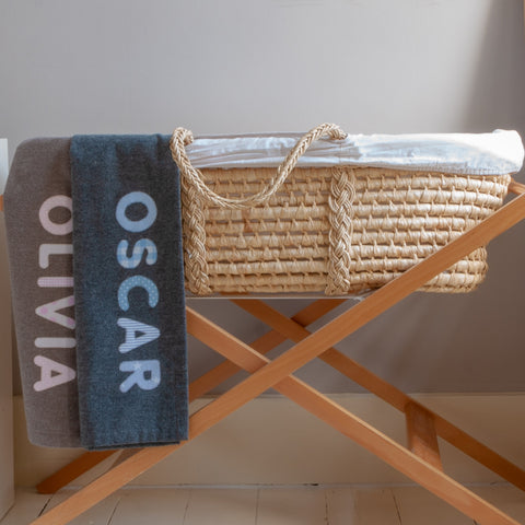 baby Moses basket with two baby blankets dropped over it