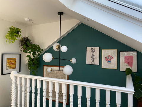 landing in a house with  green walls and an small curated art gallery wall