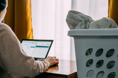 woman on laptop next to some laundry