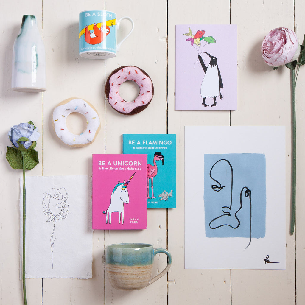 Gifted Local flat lay of books, prints, toy donuts and mugs on white floorboards