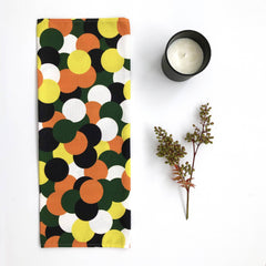 Rosha Nutt dotty tea towel on a white table with a candle