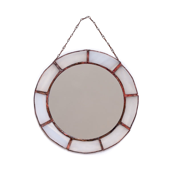 vintage looking round mirror with white glass decoration around it