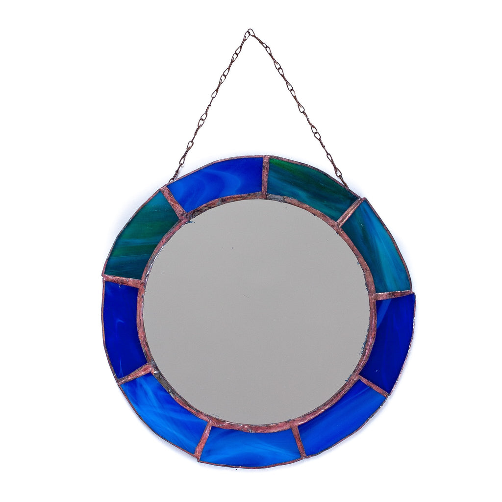 vintage looking round mirror with different blue panels decorating the outside of it