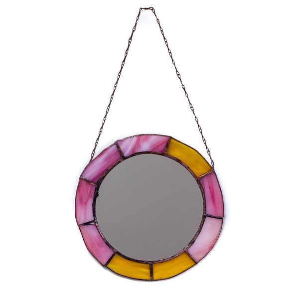 vintage looking round mirror with different yellow and pink panels decorating the outside of it