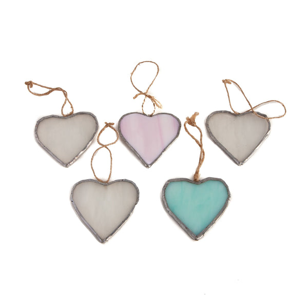 five small glass hearts attached to string in different colours