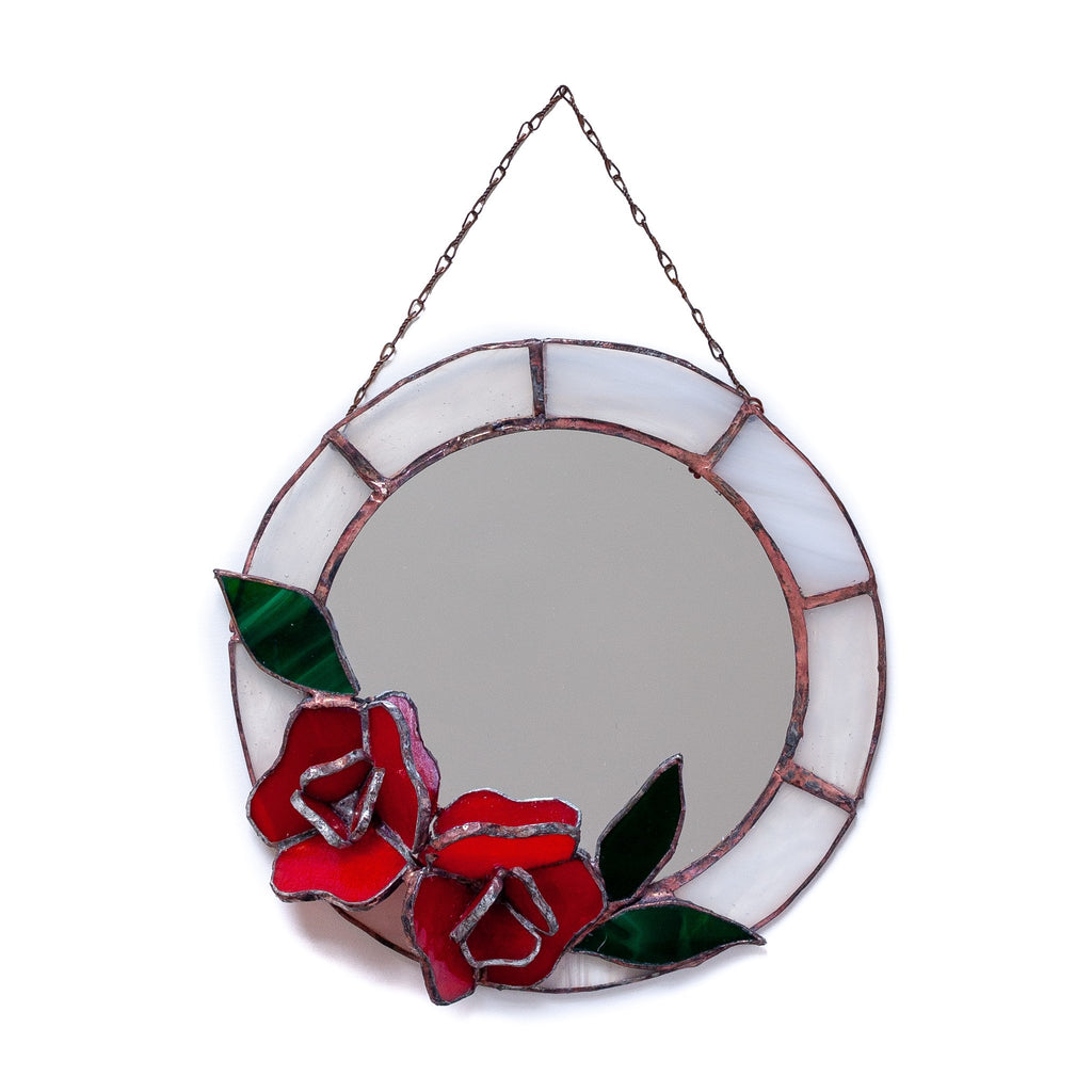 vintage looking round mirror with different white panels decorating the outside of it and glass red rose at the bottom of it