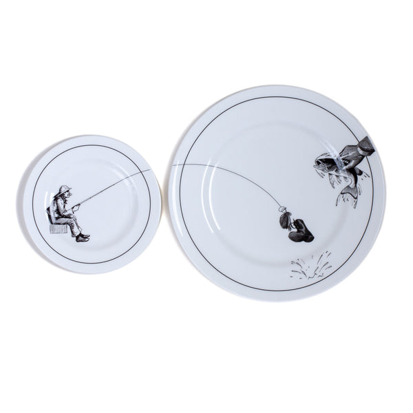 a white china dinner plate and a side plate on a grey background with a black printed design on it of a fisherman sitting down with his fishing line flowing across both plates catching a boot