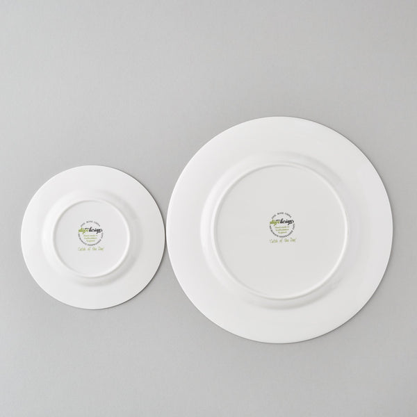 back of a white china dinner plate and the back of a white side china plate showing the care instructions and logo of the designer
