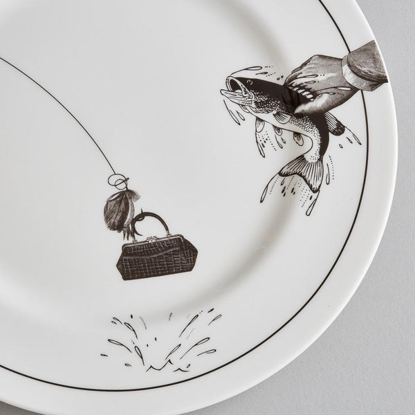 a detailed close up of a white china dinner plate and a side plate on a grey background with a black printed design on it of a fisherman sitting down with his fishing line flowing across both plates catching a fish