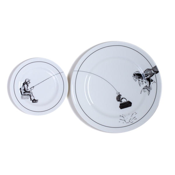 a white china dinner plate and a side plate on a grey background with a black printed design on it of a fisherman sitting down with his fishing line flowing across both plates catching a hangbag
