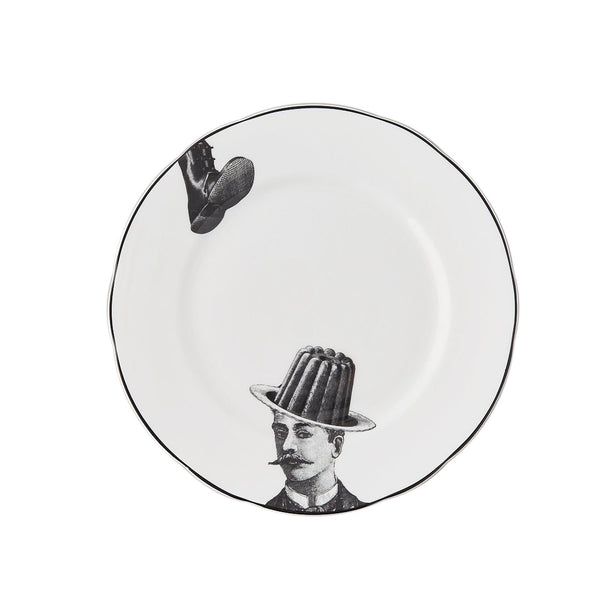 a white china dessert plate with a black printed design on it of a man with a moustache and jelly bowler hat about to be squashed by a big boot