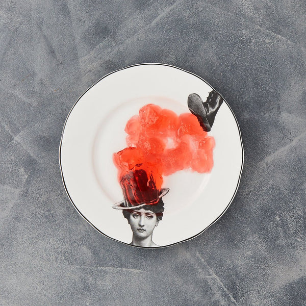 a white china dessert plate with a black printed design on it of a woman and jelly bowler hat about to be squashed by a big boot with some red jelly on the plate