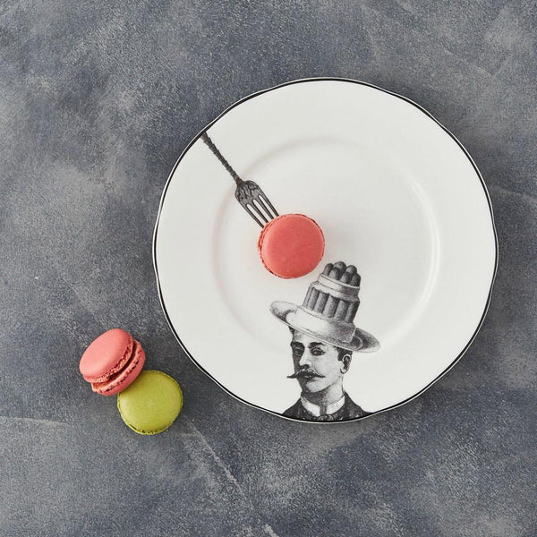 a white china dessert plate with a black printed design on it of a man with a moustache and cake bowler hat with a fork about to pick up the cake with some real macarons decorating the plate