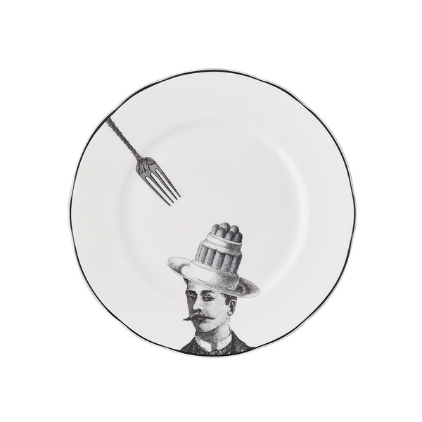 a white china dessert plate with a black printed design on it of a man with a moustache and cake bowler hat with a fork about to pick up the cake