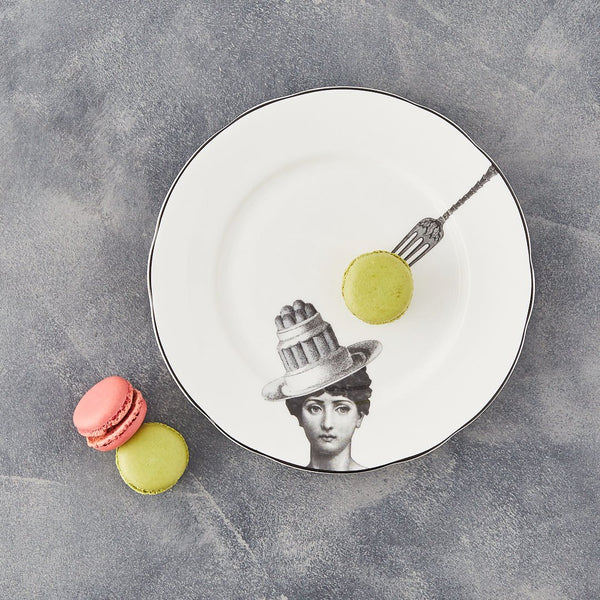 a white china dessert plate with a black printed design on it of a woman and cake bowler hat with a fork about to pick up the cake with some real macarons decorating the plate