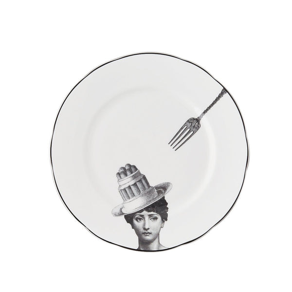 a white china dessert plate with a black printed design on it of a woman and cake bowler hat with a fork about to pick up the cake