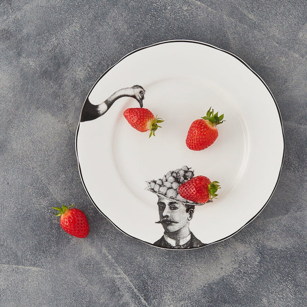 a white china dessert plate with a black printed design on it of a man with a moustache and fruit bowler hat with a fork with the head of an ostrich about to peck at the fruit with some strawberries on the plate