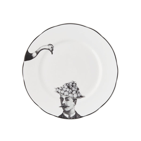 a white china dessert plate with a black printed design on it of a man with a moustache and fruit bowler hat with a fork with the head of an ostrich about to peck at the fruit
