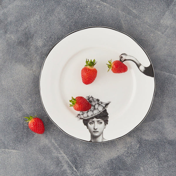 a white china dessert plate with a black printed design on it of a woman and a fruit bowler hat with a fork with the head of an ostrich about to peck at the fruit with some strawberries on the plate