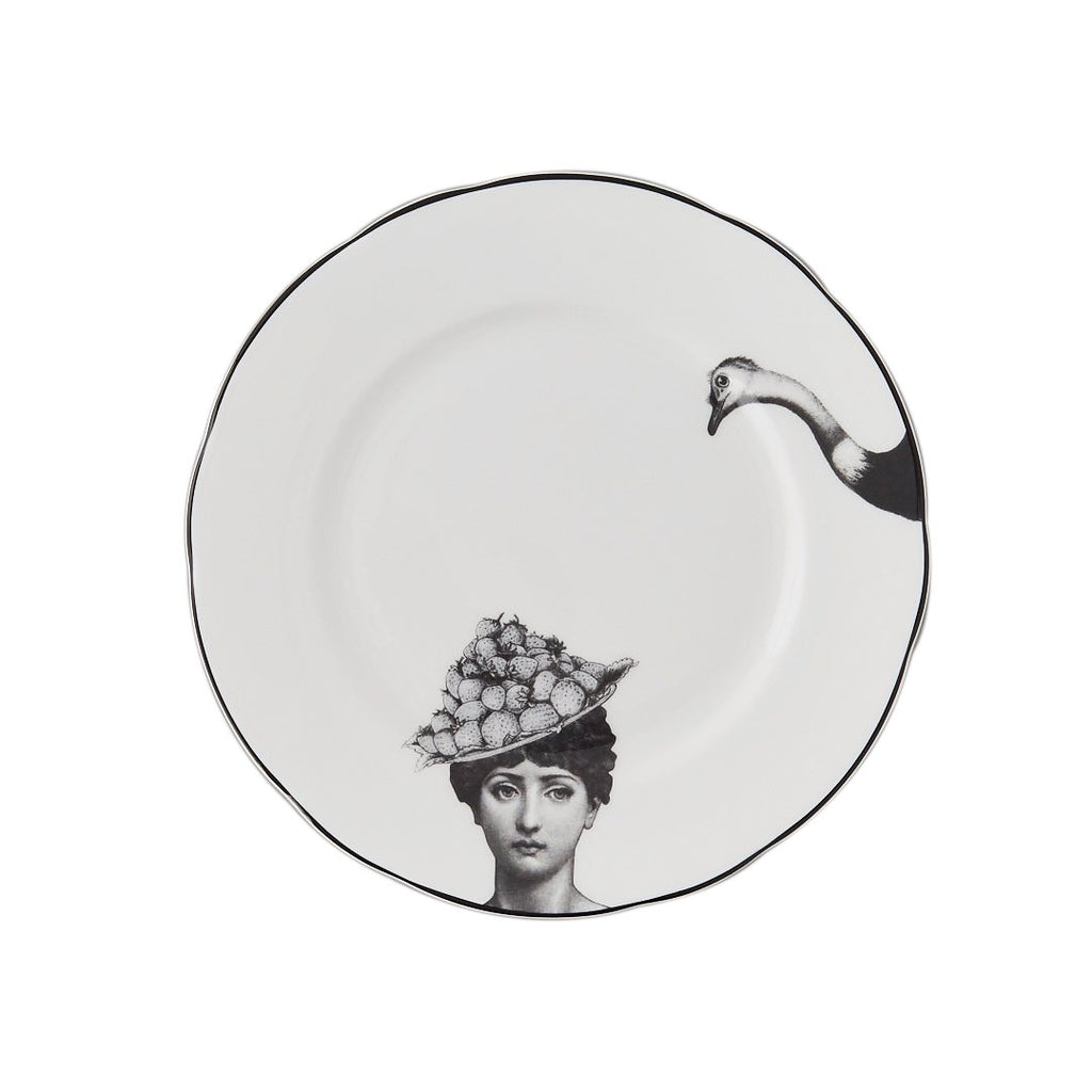 a white china dessert plate with a black printed design on it of a woman and a fruit bowler hat with a fork with the head of an ostrich about to peck at the fruit