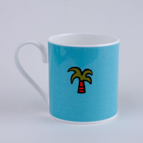 blue mug with a little green palm tree printed on it