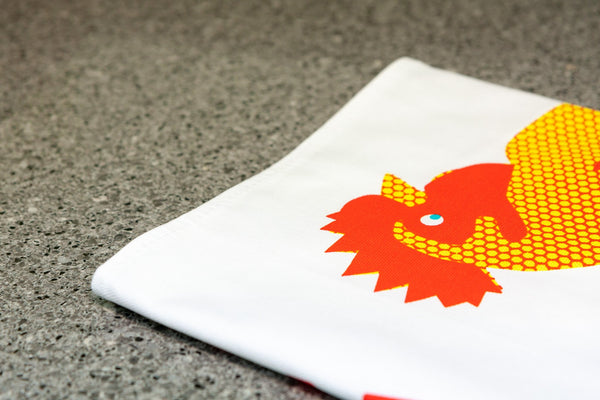detail of teatowel with a chicken printed on it with the word chicken written out