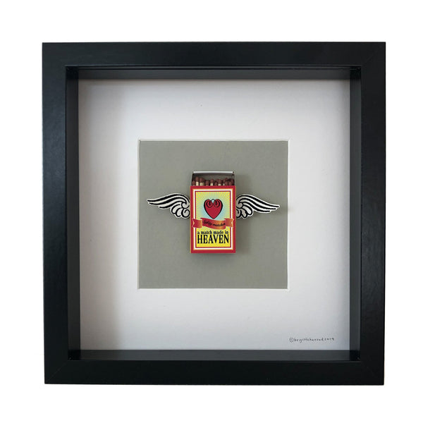 a match box mounted on a piece of card with wings coming out of it and the words a match made in heaven printed on it