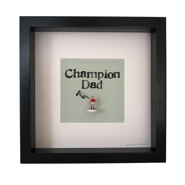a little football figure with the words champion dad over it and a finger pointing at it all in a picture frame
