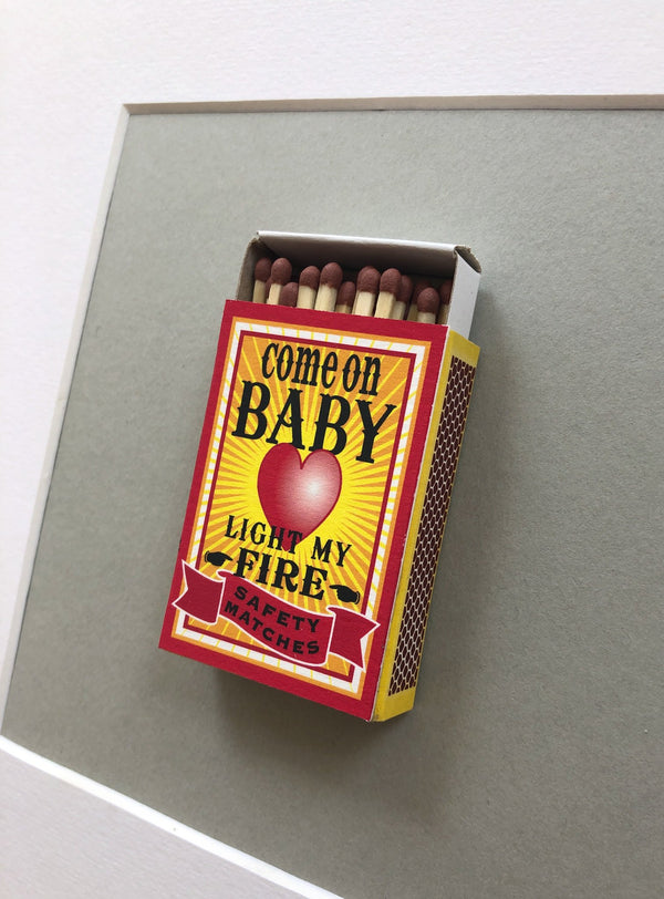 a match box mounted on a piece of card with the words come on baby light my fire printed on it
