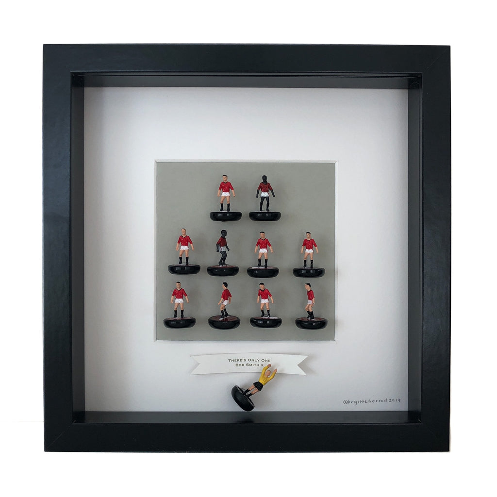 little figures of a football team mounted on a piece of card and framed with some personalised wording underneath it