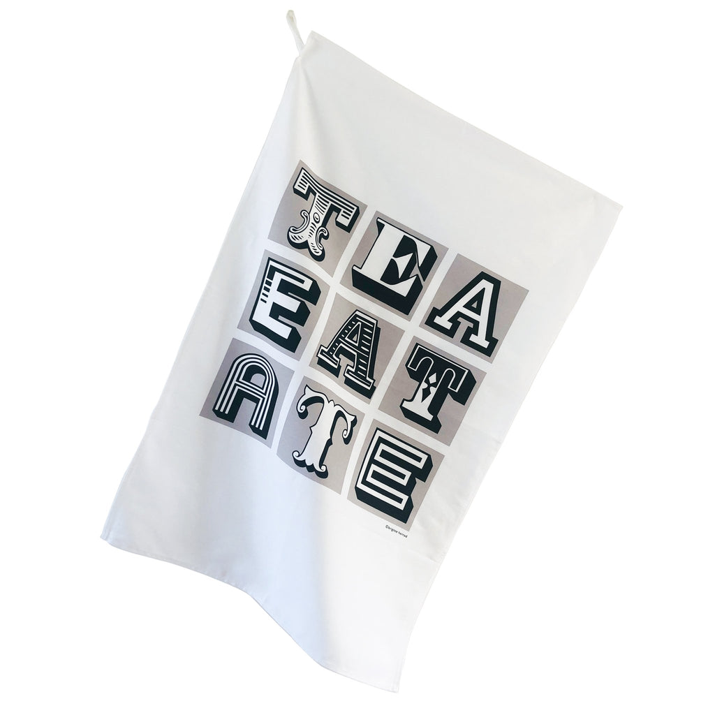 white teatowel wit black words tea eat ate printed on it