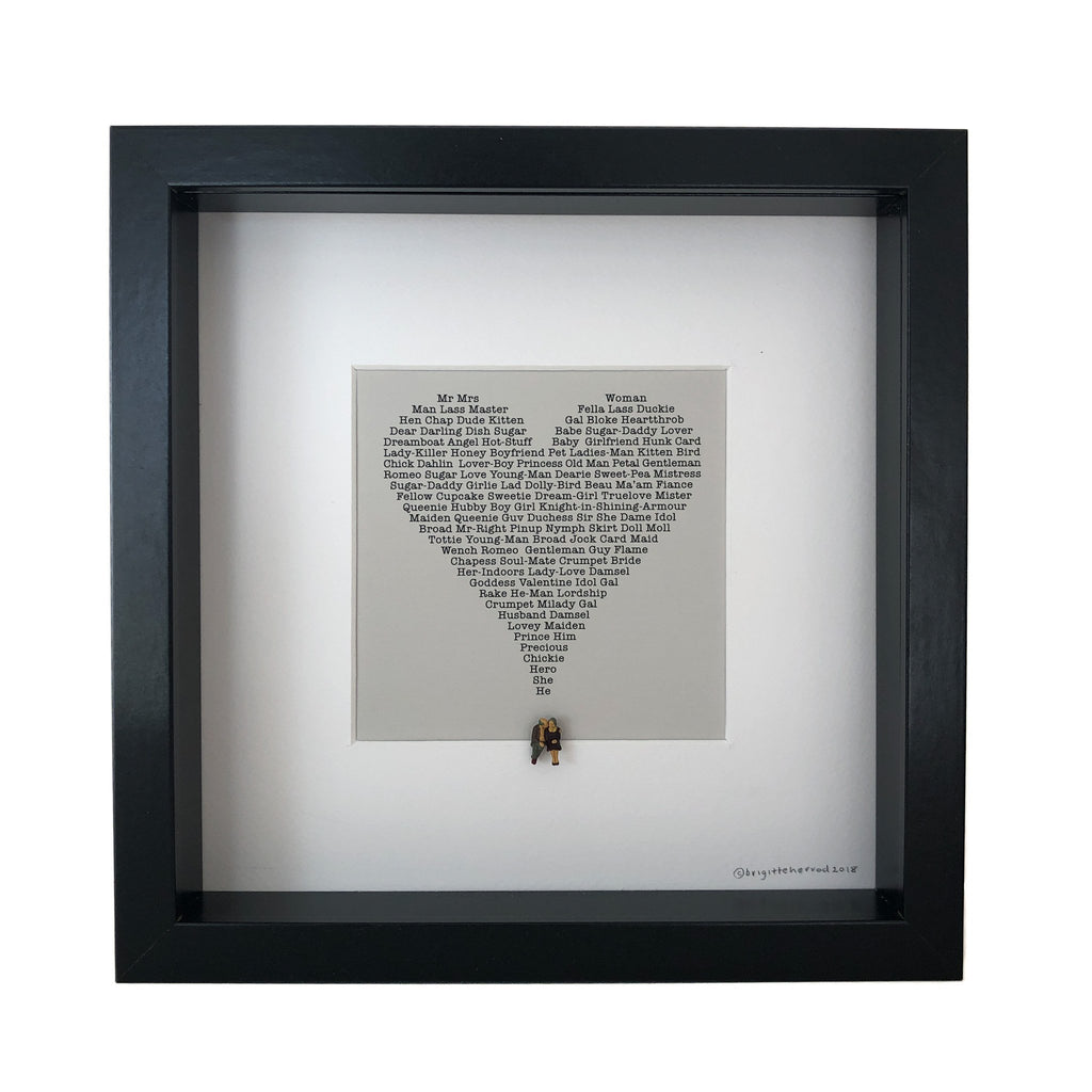 mounted picture of a heart made up of words to describe love with two little figures sitting underneath it