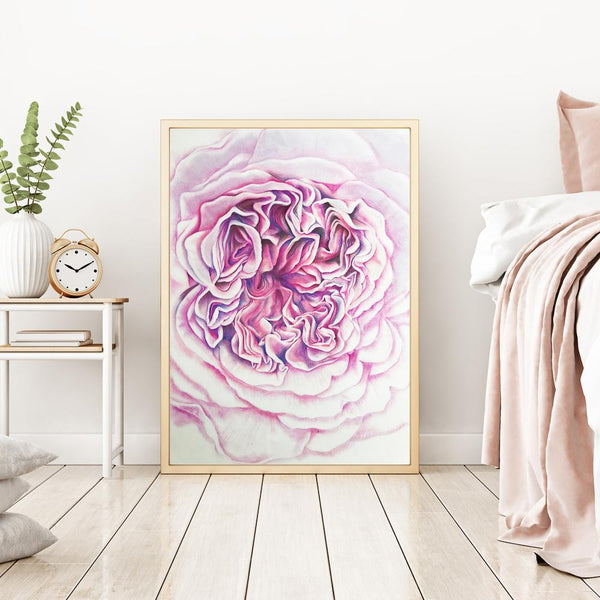 large watercolour print of the inside detail of a pink rose leaning against a wall next to a bed and bedside table