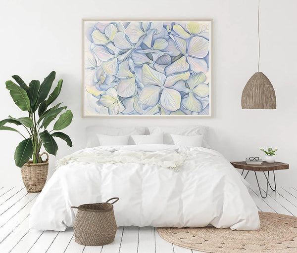 large framed watercolour print of blue hydrangea in bloom hanging above a bed with a bedside table rug laundry basket and large indoor plant