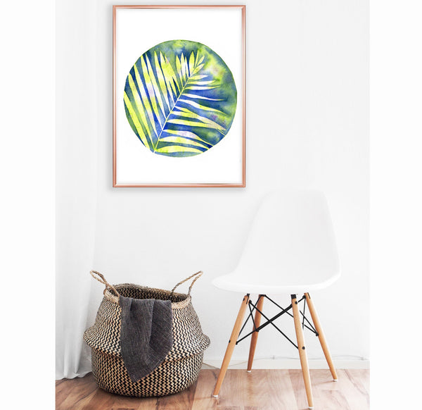 watercolour of a yellow fern plant with a blue colourful background hanging on a white wall above a white chair and wicker laundry basket