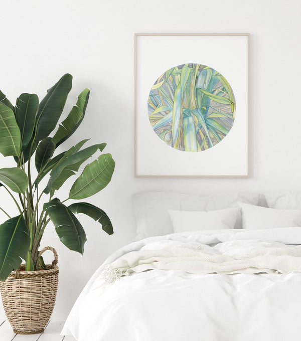 framed circular watercolour of grass in late summer night hanging above a bed and a big plant