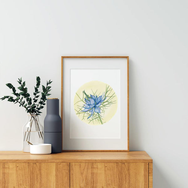 framed circular watercolour print of a blue love in a mist flower leaning on a table with a flower and vase