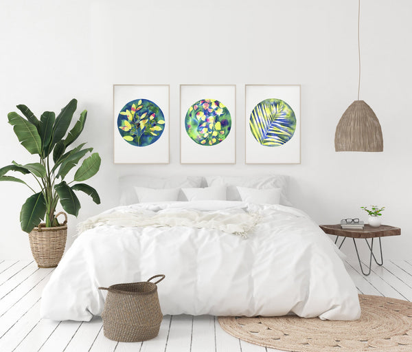 three botanical watercolours in green and pink colours hanging up above a bed with a big plant hanging light and rug